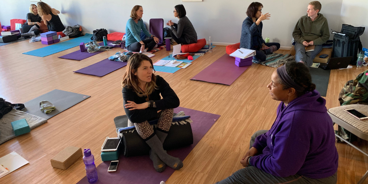 People discussing yoga training in a group setting