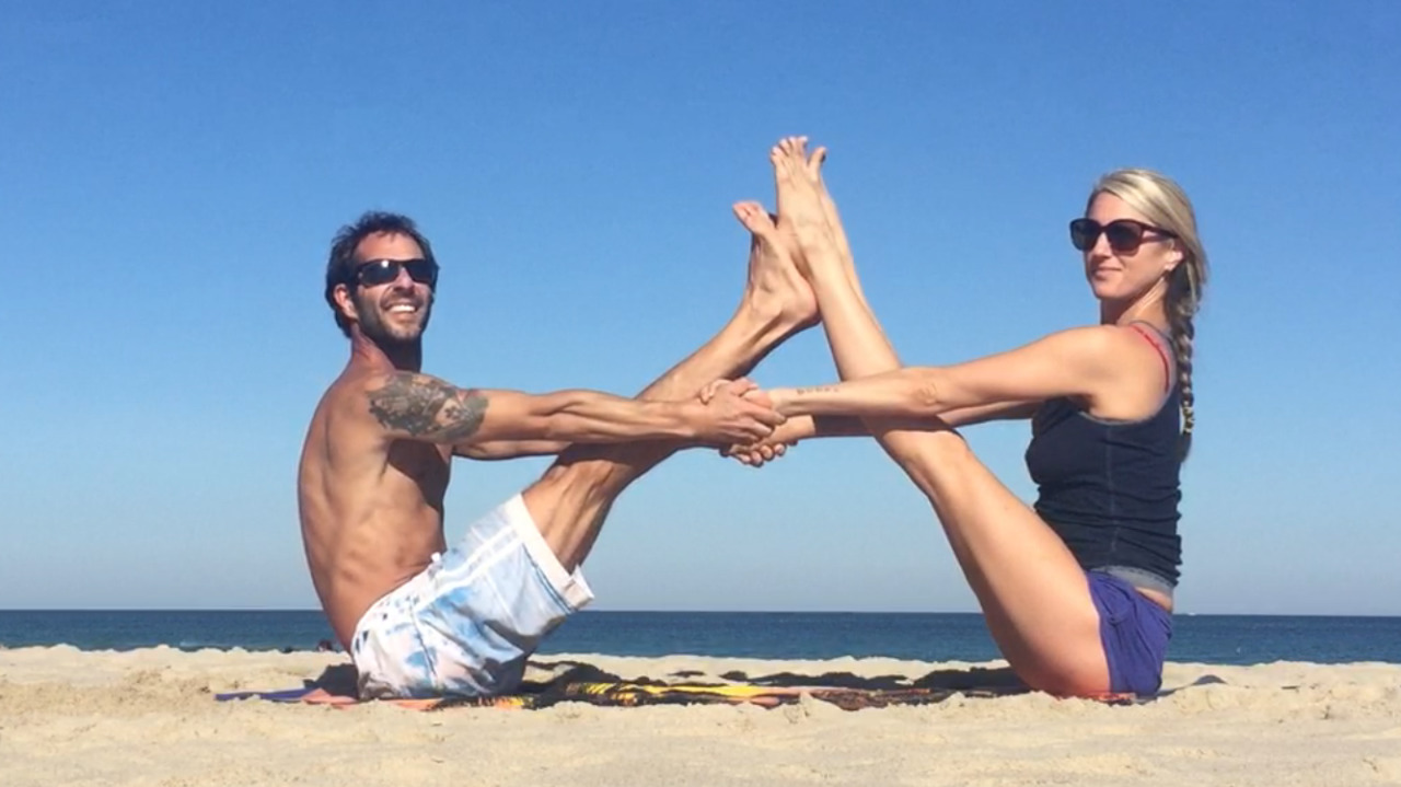 Couple-practicing-yoga-on-the-beach